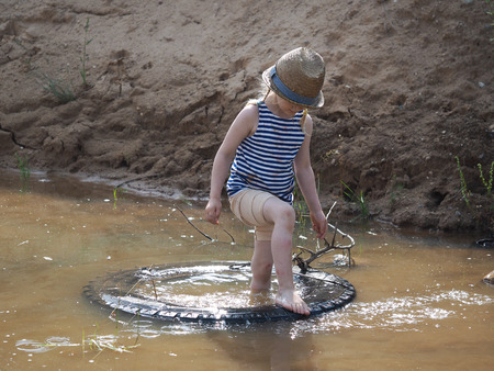 Happy little girl playing in a big puddle of sand quarry