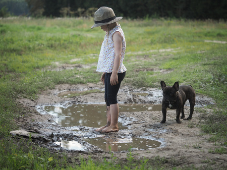 muddy: A child playing in a muddy puddle. Dirty girl in a hat and barefoot. Rural road