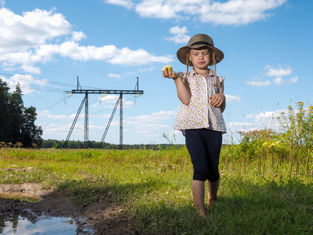 environmental issues: Child in field eating an apple. Rural road, mud and puddles. Blue sky. The girl in the hat and barefoot. The concept of the child in the village, travel Stock Photo