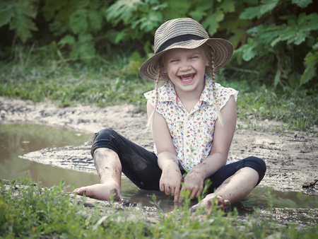 prank: Extremely dirty baby laughing sitting in a puddle