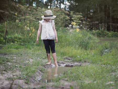 A child playing in a muddy puddle. Dirty girl in a hat and barefoot. Rural road