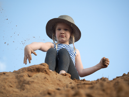 Child on the mountain of sand. Blue sky. A little girl throws sand. Journey with the concept of children Фото со стока