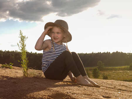 The child is sitting on a mountain of sand. A little girl, wearing a hat and barefoot. Journey with the concept of children