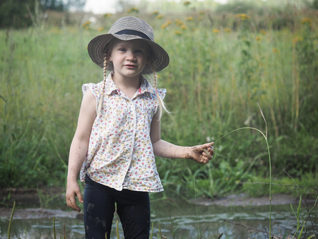 Portrait of a grimy child in a field. The girl in the hat