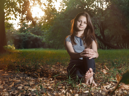 girl sitting in autumn Park. A lot of autumn leaves Stock Photo