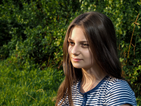 Portrait of a beautiful young girl with long brown hair. Summer, green grass, nature