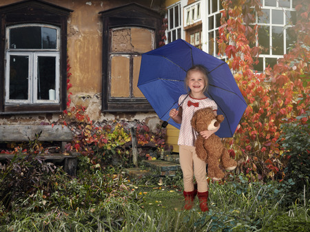 The child is under the blue umbrella with a toy bear. Farmland, farmhouse, garden. Autumn, red vines on the Windows of the house Stock Photo