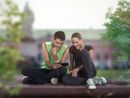software portability: couple of teenagers sitting on the school grounds and watch in mobile phone