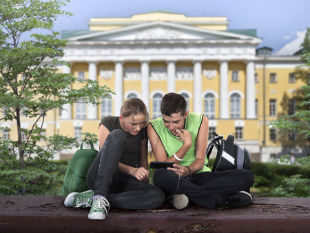 software portability: teenagers sitting on the school grounds and watch in mobile phone