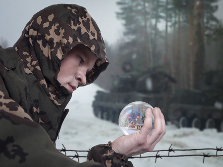 young soldier in camouflage clothing. Portrait. The military is looking at a glass Christmas ball. In ball of a winter landscape, house, snow. Stock Photo