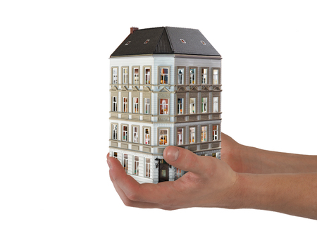 Hands holding a house with many apartments