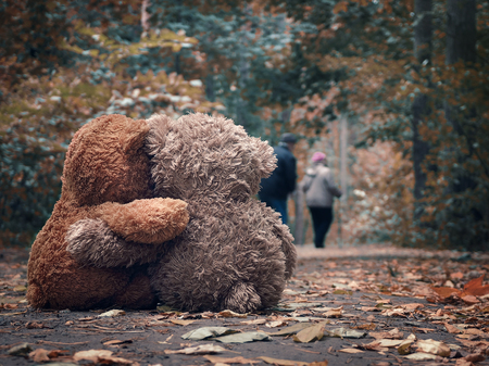 Two Teddy bear hugging each other and watch out for the road an elderly couple of people - grandparents Imagens - 87599756