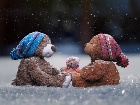 Toys Teddy bears sitting under falling snow. The concept of family, parents and child together Stock Photo