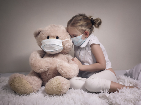 Little girl and big plush bear in medical masks. The concept of childhood diseases, empathy, support and help sick children Фото со стока