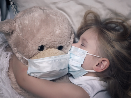 Little girl and big plush bear sleep in medical masks. The concept of childhood diseases, empathy, support and help sick children