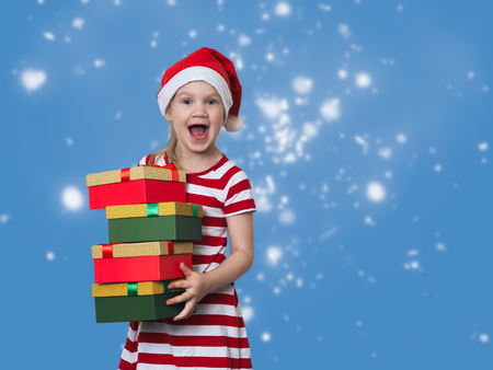 Happy child with a mountain of gifts. Emotional portrait. Delight girls in Christmas hat