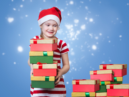 disbelief: Happy child looks at a mountain of gifts. Little girl in Christmas hat