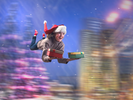 Incredibly happy girl flying with gifts in hand. Christmas hat. Background, speed, night city. The concept of Christmas sales, new year discounts Stock Photo
