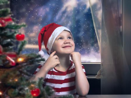 Little girl in Christmas hat dreams. Emotive portrait of happy child