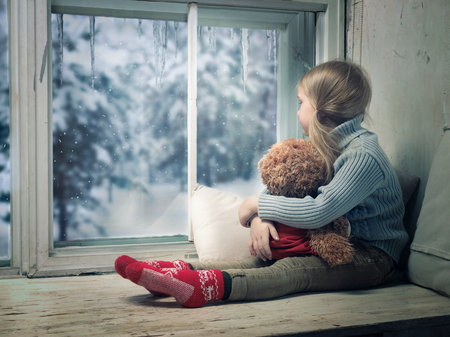 Little girl looking out the window. Outside, the winter snow. Imagens - 90279499