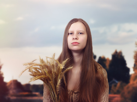 Beautiful natural beauty Russian girl with ears of wheat. Field, blue sky