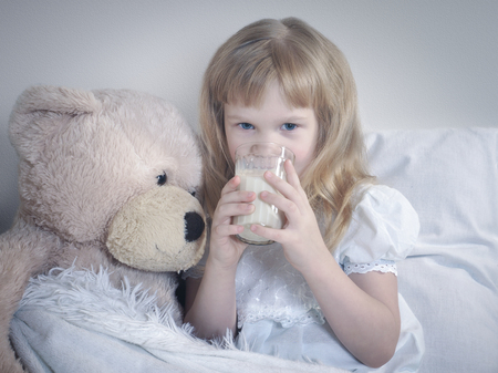 Little girl drinks milk before bedtime. Child in bed with toy - big white bear