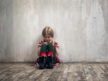 Trauriges kleines Mädchen, das auf dem Boden sitzt. Das Konzept der Kinderpsychologie, Einsamkeit, Ressentiments