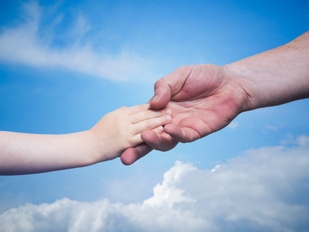 fathers hand holding the hand of your child on blue sky background, the concept of the family trust, mutual support Stock Photo