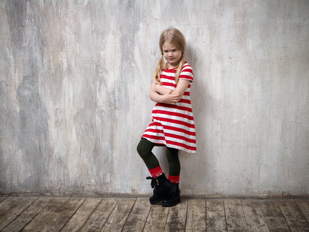 A punished child standing by the wall. Concept problems of education of children, childrens resentment, loneliness