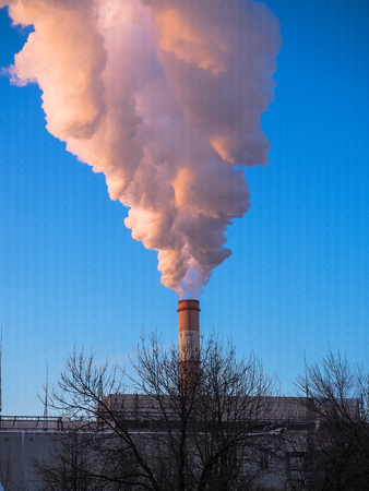 Pink smoke from the chimney of heating plant during sunset. Stock Photo