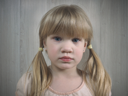 Little girl. On the cheek of the child tear. Emotional portrait of an offended child