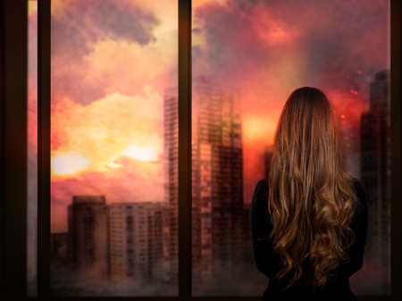 The girl looks through the window at the burning city. Concept - war, natural disasters, the death of mankind Stock Photo