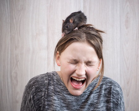 The girl in panic shouting. On her head sits a rat. The concept of a phobia, a fear of rodents, inner fears, hallucinations