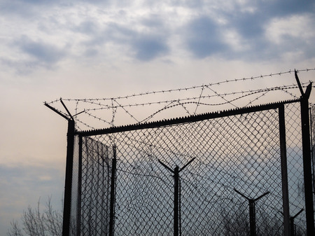 Fence with barbed wire on sky background