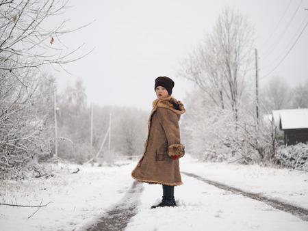 Portrait of child. Beautiful winter road, snow Banco de Imagens