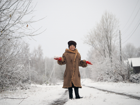 Portrait of a cheerful girl with a snowball in her hands