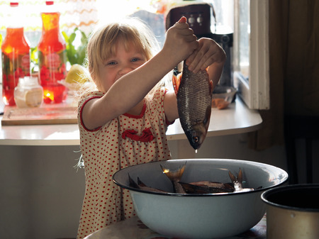 The child holding the tail of the fish, the roach. Girl in the kitchen helps to disassemble the fish catch