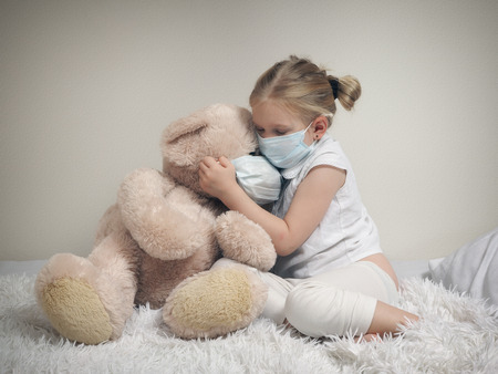 A child in a medical mask on the bed with a big toy bear Foto de archivo