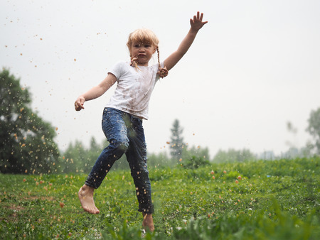 A child jumping in a puddle. The moment of the girl's jump-splashes, drops of water, speed of movement Banque d'images - 115398560