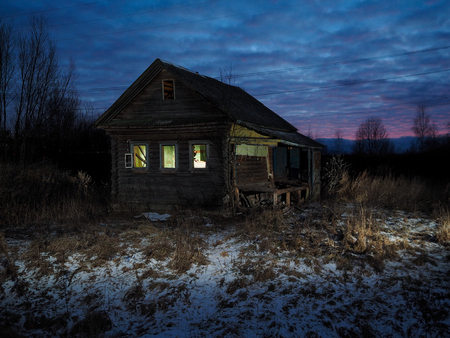 Mystical abandoned house. Night. Strange light in Windows