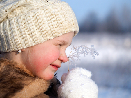 Childs face. Smile. Icy branch of the plant. The concept of the changing weather, cold, environment
