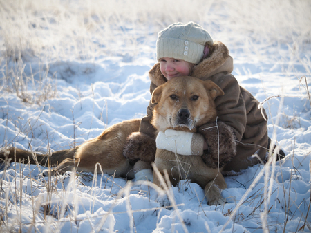 The child hugs the dog. Very cold. Icy plants. Much snow. Unexpected cold, winter Banque d'images - 115398685