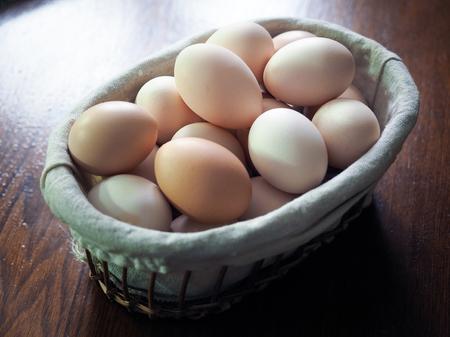 Eggs in wicker basket on a wooden table