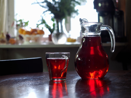 Jug and glass with red drink on the table Imagens