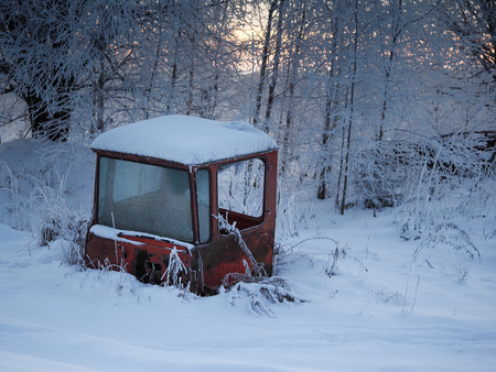 An abandoned old agricultural machinery, parts of the tractor in the snow drifts