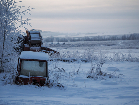 An abandoned old agricultural machinery, parts of the tractor in the snow drifts Banque d'images - 115398865