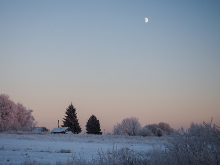 Winter rural landscape. Roofs of village houses, trees, field. Imagens