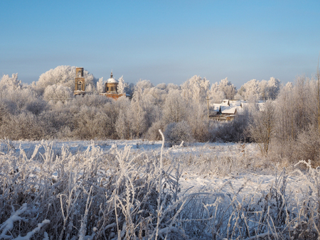 Winter rural landscape. The village, the temple destroyed from time. Snow-covered trees