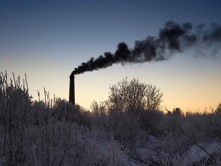 Black smoke from pipes. Icy grass and trees