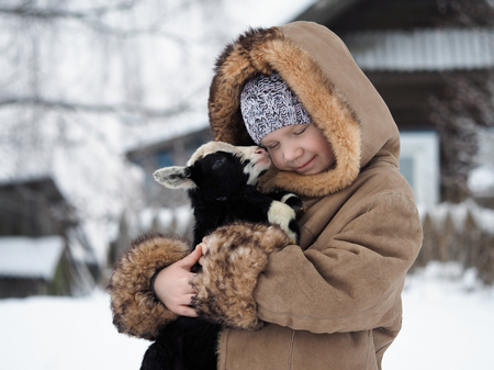 Happy little girl with a newborn lamb in her arms. Winter, cold. Village life in Russia